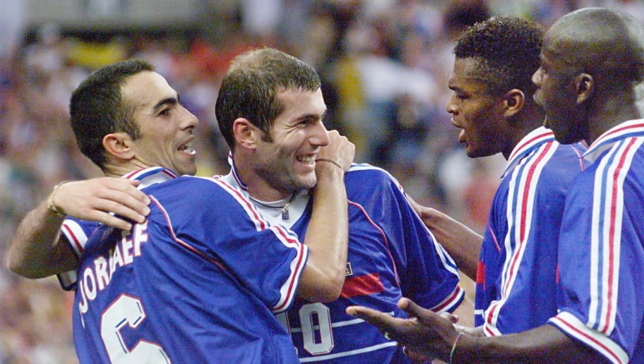 Photo prise le 12 juillet 1998 au Stade de France à Saint Denis, du milieu de terrain de l'équipe de France de football Zinedine Zidane (2eG), félicité par ses coéquipiers, Youri Djorkaeff (G), Marcel Desailly (2eD) et Lilian Thuram (D), après son deuxième but face à l'équipe du Brésil lors de la finale de la Coupe du Monde.   French Zinedine Zidane (2nd L) is hugged by teammate Youri Djorkaeff (L) as they celebrate with Marcel Desailly (2nd R) and Lilian Thuram (R) after Zidane scored  a second goal for their team 12 July at the Stade de France in Saint-Denis, near Paris,  during the 1998 Soccer World Cup final match between Brazil and France. (ELECTRONIC IMAGE)        (Photo credit should read GABRIEL BOUYS/AFP/Getty Images)