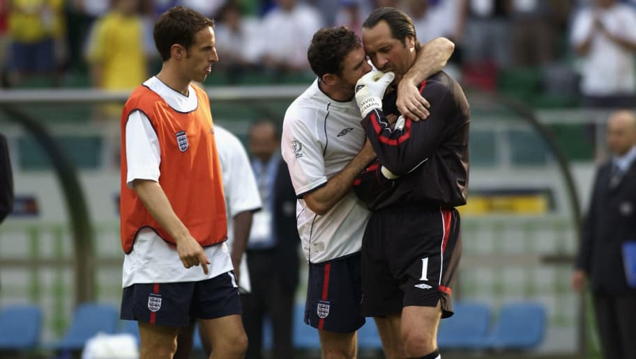 SHIZUOKA - JUNE 21:  Martin Keown (centre) consoles David Seaman (right) of England after the England v Brazil World Cup Quarter Final match played at the Shizuoka Stadium Ecopa in Shizuoka, Japan on June 21, 2002. Brazil won the match 2-1. (Photo by Stu Forster/Getty Images)