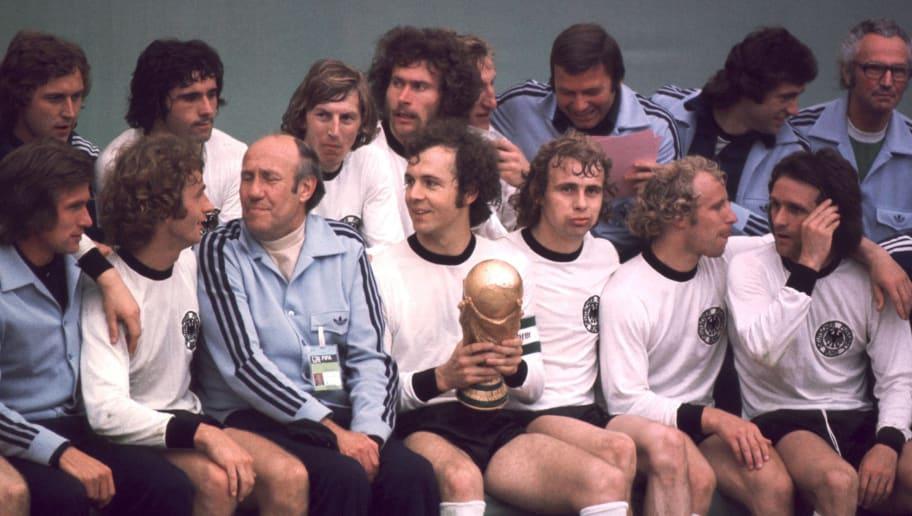 MUNICH, GERMANY - JULY 07:  FUSSBALL: WM 1974/Weltmeisterschaft 1974, hintere Reihe v.l.: Heinz FLOHE, Gerd MUELLER, Juergen GRABOWSKI, Paul BREITNER, SCHWARZENBEK, ?, Bernd CULLMANN, ?, vordere Reihe v.l.: Jupp HEYNCKES, Rainer BONHOF, Trainer Helmut SCHOEN, Franz BECKENBAUER (mit Pokal), Bernd HOELZENBEIN, Berti VOGTS, Wolfgang OVERATH  (Photo by Bongarts/Getty Images)