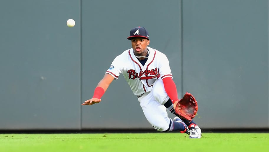 ATLANTA, GA - OCTOBER 08:  Ronald Acuna Jr. #13 of the Atlanta Braves attempts a catch on a hit by Yasiel Puig #66 of the Los Angeles Dodgers during the second inning of Game Four of the National League Division Series at Turner Field on October 8, 2018 in Atlanta, Georgia.  (Photo by Scott Cunningham/Getty Images)