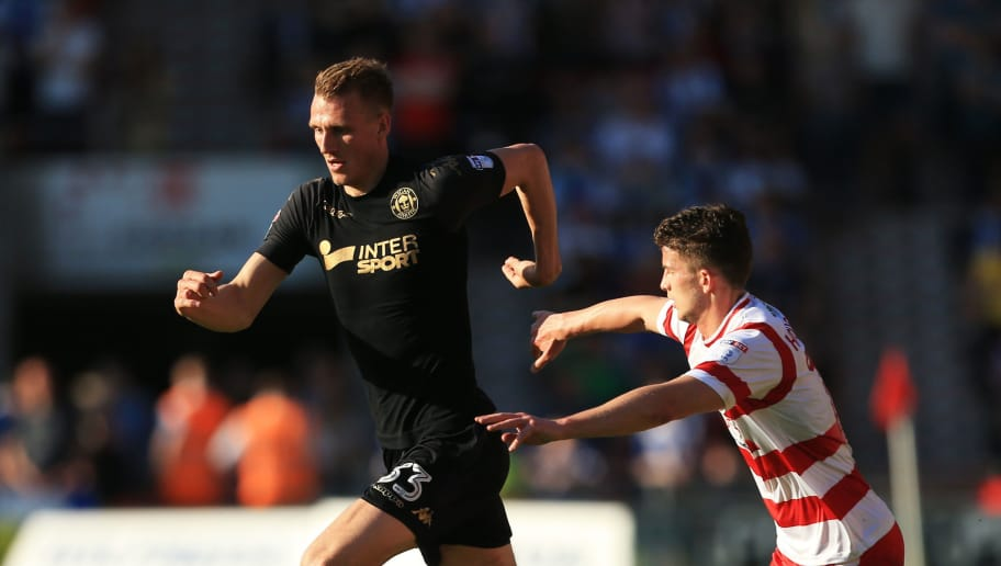DONCASTER, ENGLAND - MAY 05:  Dan Burn of Wigan Athletic controls the ball as Declan Ogley of Doncaster Rovers chases during the Sky Bet League One match between Doncaster Rovers and Wigan Athletic at Keepmoat Stadium on May 5, 2018 in Doncaster, England.  (Photo by Stephen Pond/Getty Images)