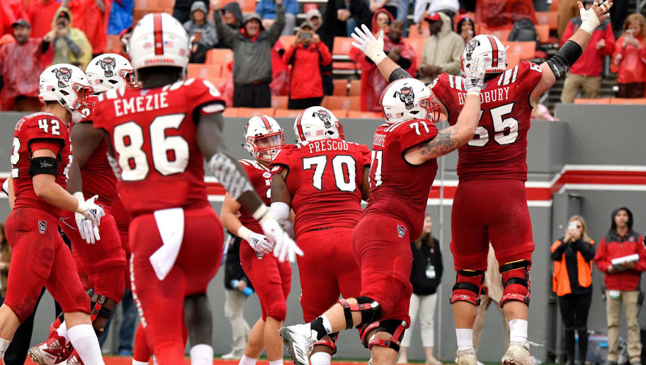 RALEIGH, NC - DECEMBER 01: Garrett Bradbury #65 of the North Carolina State Wolfpack celebrates with teammates following a one-yard touchdown run against the East Carolina Pirates in the fourth quarter at Carter-Finley Stadium on December 1, 2018 in Raleigh, North Carolina. NC State won 58-3. (Photo by Lance King/Getty Images)