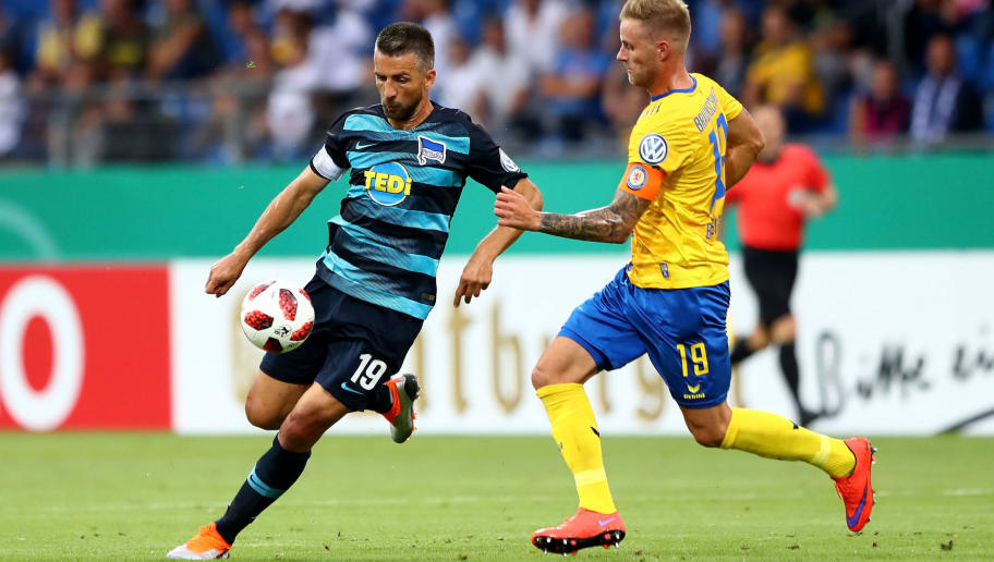 BRAUNSCHWEIG, GERMANY - AUGUST 20:  Felix Burmeister (R) of Braunschweig and Vedad Ibisevic of Berlin battle for the ball during the DFB Cup first round match between Eintracht Braunschweig and Hertha BSC at Eintracht Stadion on August 20, 2018 in Braunschweig, Germany.  (Photo by Martin Rose/Bongarts/Getty Images)