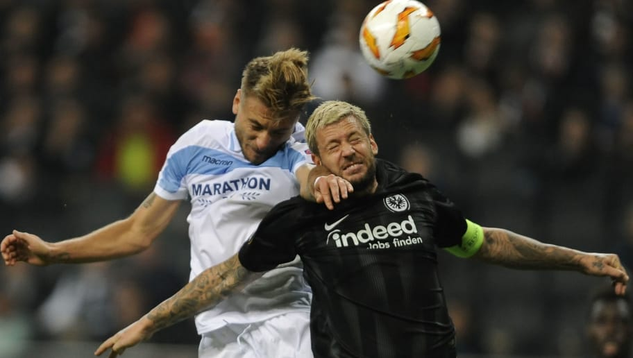 FRANKFURT AM MAIN, GERMANY - OCTOBER 04:  Ciro Immobile of SS Lazio compete for the ball with Marco Russ of Eintracht Frankfurt during the UEFA Europa League Group H match between Eintracht Frankfurt and SS Lazio at Commerzbank-Arena on October 4, 2018 in Frankfurt am Main, Germany.  (Photo by Marco Rosi/Getty Images)