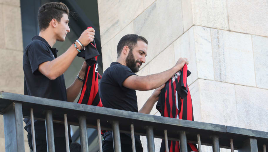 New AC Milan players Argentinian Gonzalo Higuain (R) and Italian Mattia Caldara, show their jerseys to fans from a balcony, on Milan's central Piazza Duomo square on August 3, 2018. (Photo by - / AFP)        (Photo credit should read -/AFP/Getty Images)
