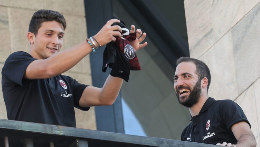 New AC Milan players Argentinian Gonzalo Higuain (R) and Italian Mattia Caldara, wave to fans from a balcony, on Milan's central Piazza Duomo square on August 3, 2018. (Photo by - / AFP)        (Photo credit should read -/AFP/Getty Images)