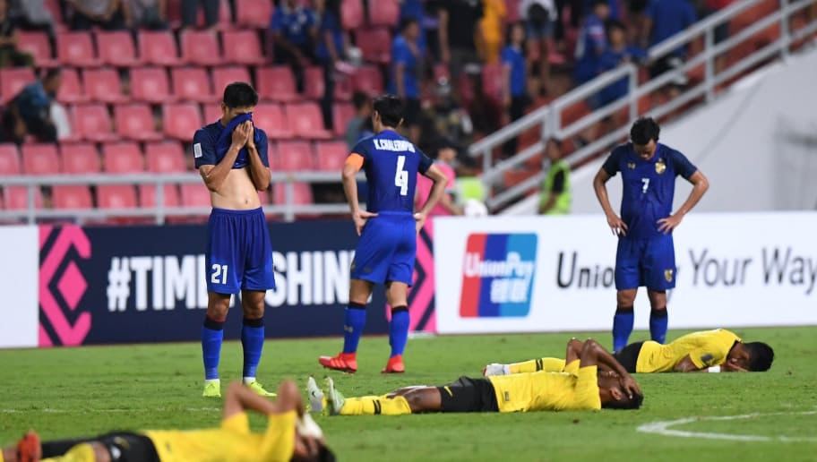 Malaysian and Thailand (standing) players react at the end of the second leg of the AFF Suzuki Cup 2018 semifinal football match between Thailand and Malaysia at the Rajamangala Stadium in Bangkok on December 5, 2018. (Photo by Lillian SUWANRUMPHA / AFP)        (Photo credit should read LILLIAN SUWANRUMPHA/AFP/Getty Images)