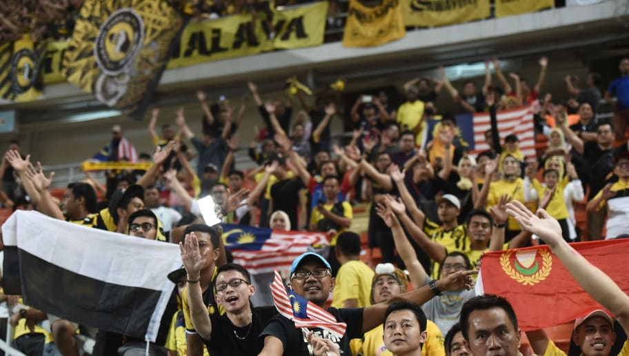 Malaysian fans celebrate at the end of the second leg of the AFF Suzuki Cup 2018 semifinal football match between Thailand and Malaysia at the Rajamangala Stadium in Bangkok on December 5, 2018. (Photo by Lillian SUWANRUMPHA / AFP)        (Photo credit should read LILLIAN SUWANRUMPHA/AFP/Getty Images)