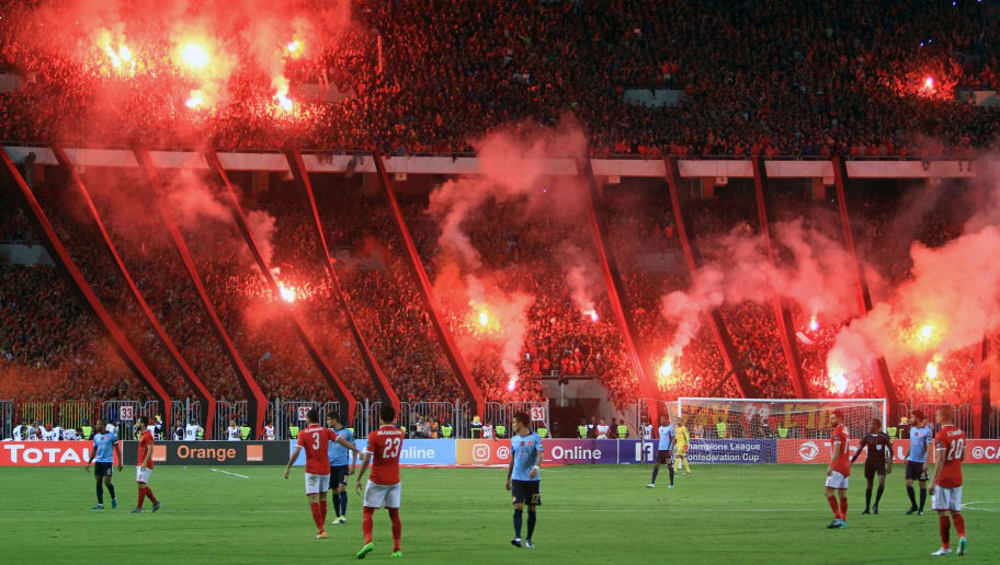 Al-Ahly supporters carry flares during the CAF Champions League final football match between Al-Ahly vs Wydad Casablanca at the Borg El Arab Stadium in Alexandria on October 28, 2017. / AFP PHOTO / STRINGER        (Photo credit should read STRINGER/AFP/Getty Images)