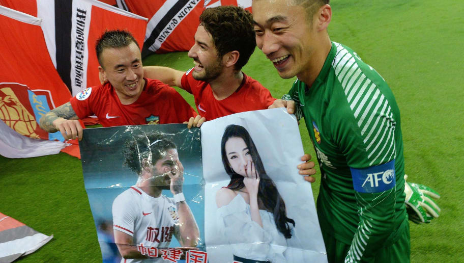 This picture taken on March 14, 2018 shows Alexandre Pato of Tianjin Quanjian (C) holding a poster, showing pictures of him and Chinese actress Dilraba Dilmurat, with teammates Wang Yongpo (L) and Zhang Lu after the AFC Champions League group stage football match between China's Tianjin Quanjian and South Korea's Jeonbuk Hyundai in Tianjin. The poster reads, 'Pa Jianguo, play well, Dilraba is watching the live broadcast.' Brazilian football star Alexandre Pato celebrated Tianjin Quanjian's victory in the AFC Champions League with a very public attempt at wooing the Chinese actress Dilraba Dilmurat. / AFP PHOTO / - / China OUT (Photo credit should read -/AFP/Getty Images)