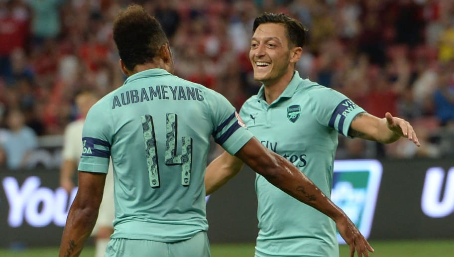 Arsenal's Mesut Ozil (R) celebrates with teammate Pierre-Emerick Aubameyang after scoring during the International Champions Cup football match between Arsenal and Paris Saint-Germain in Singapore on July 28, 2018. (Photo by ROSLAN RAHMAN / AFP)        (Photo credit should read ROSLAN RAHMAN/AFP/Getty Images)