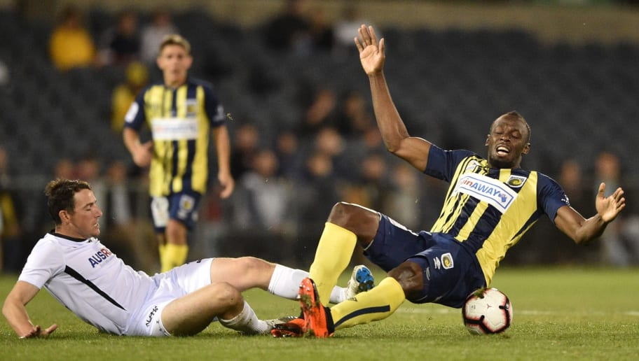 Olympic sprinter Usain Bolt (R) playing for A-League football club Central Coast Mariners is tackled by Josh Symons of Macarthur South West United (L) in his first competitive start for the club in Sydney on October 12, 2018. (Photo by PETER PARKS / AFP) / -- IMAGE RESTRICTED TO EDITORIAL USE - STRICTLY NO COMMERCIAL USE --        (Photo credit should read PETER PARKS/AFP/Getty Images)