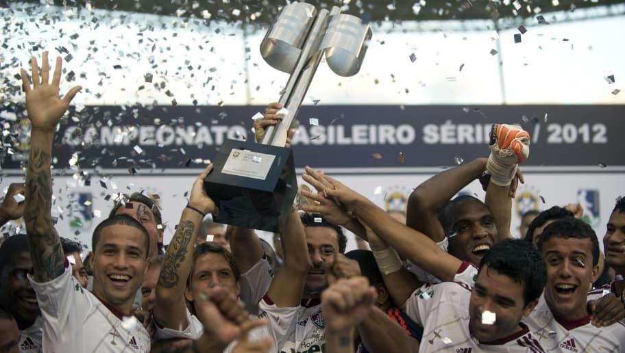 Fluminense's players celebrate with the Brazilian Football Championship trophy on November 18, 2012 at the Joao Havelange stadium in Rio de Janeiro, Brazil.  AFP  PHOTO /  ANTONIO SCORZA        (Photo credit should read ANTONIO SCORZA/AFP/Getty Images)