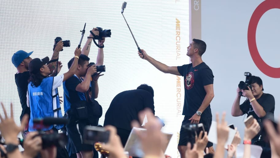 Portuguese footballer Cristiano Ronaldo uses a mobile phone to take a picture as he attends a promotional event in Beijing on July 19, 2018. (Photo by WANG ZHAO / AFP)        (Photo credit should read WANG ZHAO/AFP/Getty Images)