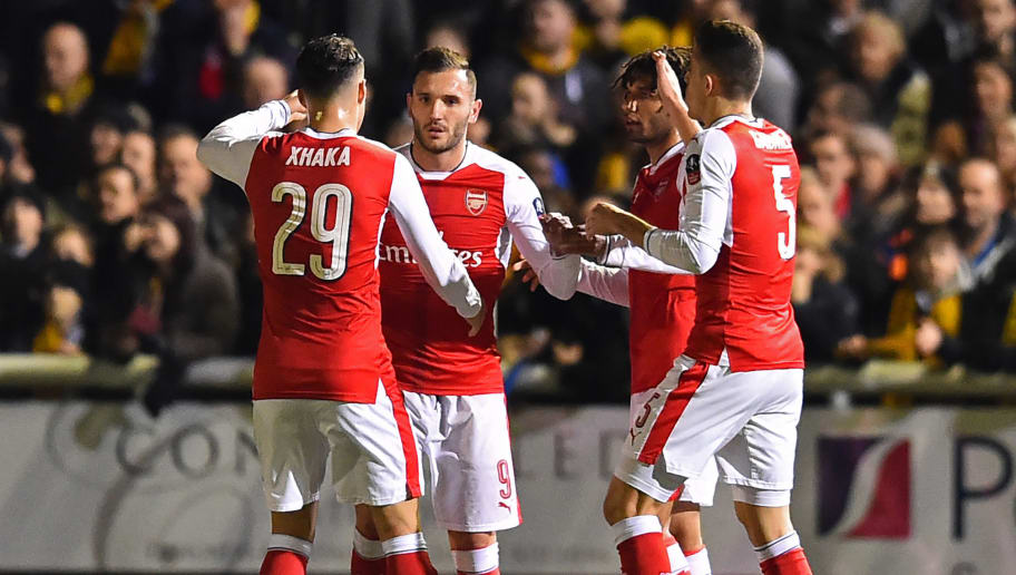 Arsenal's Spanish striker Lucas Perez (2nd L) celebrates with teammates after scoring the opening goal of the English FA Cup fifth round football match between Sutton United and Arsenal at the Borough Sports Ground, Gander Green Lane in south London on February 20, 2017. / AFP / Glyn KIRK / RESTRICTED TO EDITORIAL USE. No use with unauthorized audio, video, data, fixture lists, club/league logos or 'live' services. Online in-match use limited to 75 images, no video emulation. No use in betting, games or single club/league/player publications.  /         (Photo credit should read GLYN KIRK/AFP/Getty Images)
