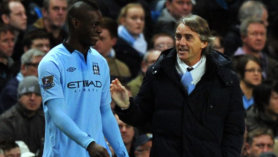 """Manchester City's Mario Balotelli (L) listens to manager Roberto Mancini when coming on as a substitute during the English FA Cup third round football match between Manchester City and Watford at The Etihad stadium in Manchester, north-west England on January 5, 2013. AFP PHOTO/PAUL ELLIS  RESTRICTED TO EDITORIAL USE. No use with unauthorized audio, video, data, fixture lists, club/league logos or """"live"""" services. Online in-match use limited to 45 images, no video emulation. No use in betting, games or single club/league/player publications.        (Photo credit should read PAUL ELLIS/AFP/Getty Images)"""