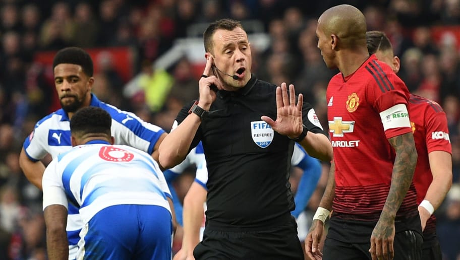 Referee Stuart Attwell (C) gestures to Manchester United's English midfielder Ashley Young (R) as he consults the Video Assistant Referee (VAR) after Manchester United's Brazilian midfielder Fred put the ball in the back of the net, before ruling out the Fred goal and awarding a penalty for a foul on Manchester United's Spanish midfielder Juan Mata, which Mata scored for the opening goal, during the English FA Cup third round football match between Manchester United and Reading at Old Trafford in Manchester, north west England, on January 5, 2019. (Photo by Oli SCARFF / AFP) / RESTRICTED TO EDITORIAL USE. No use with unauthorized audio, video, data, fixture lists, club/league logos or 'live' services. Online in-match use limited to 120 images. An additional 40 images may be used in extra time. No video emulation. Social media in-match use limited to 120 images. An additional 40 images may be used in extra time. No use in betting publications, games or single club/league/player publications. /         (Photo credit should read OLI SCARFF/AFP/Getty Images)