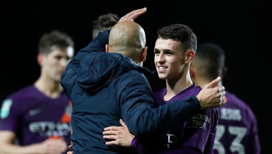 Manchester City's Spanish manager Pep Guardiola (C) hugs Manchester City's English midfielder Phil Foden during the English League Cup third round football match between Oxford United and Manchester City at the Kassam Stadium in Oxford, west of London, on September 25, 2018. (Photo by Adrian DENNIS / AFP) / RESTRICTED TO EDITORIAL USE. No use with unauthorized audio, video, data, fixture lists, club/league logos or 'live' services. Online in-match use limited to 120 images. An additional 40 images may be used in extra time. No video emulation. Social media in-match use limited to 120 images. An additional 40 images may be used in extra time. No use in betting publications, games or single club/league/player publications. /         (Photo credit should read ADRIAN DENNIS/AFP/Getty Images)
