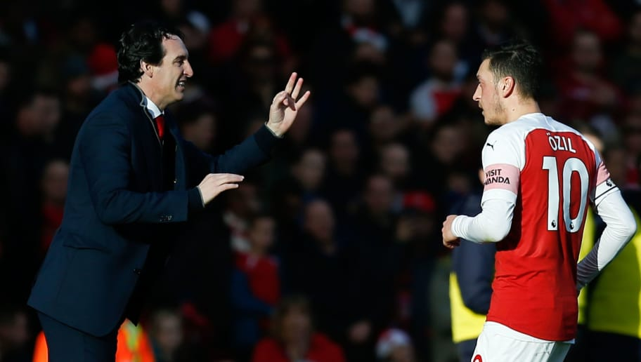 Arsenal's Spanish head coach Unai Emery (L) talks with Arsenal's German midfielder Mesut Ozil (R) during the English Premier League football match between Arsenal and Burnley at the Emirates Stadium in London on December 22, 2018. (Photo by Ian KINGTON / AFP) / RESTRICTED TO EDITORIAL USE. No use with unauthorized audio, video, data, fixture lists, club/league logos or 'live' services. Online in-match use limited to 120 images. An additional 40 images may be used in extra time. No video emulation. Social media in-match use limited to 120 images. An additional 40 images may be used in extra time. No use in betting publications, games or single club/league/player publications. /         (Photo credit should read IAN KINGTON/AFP/Getty Images)