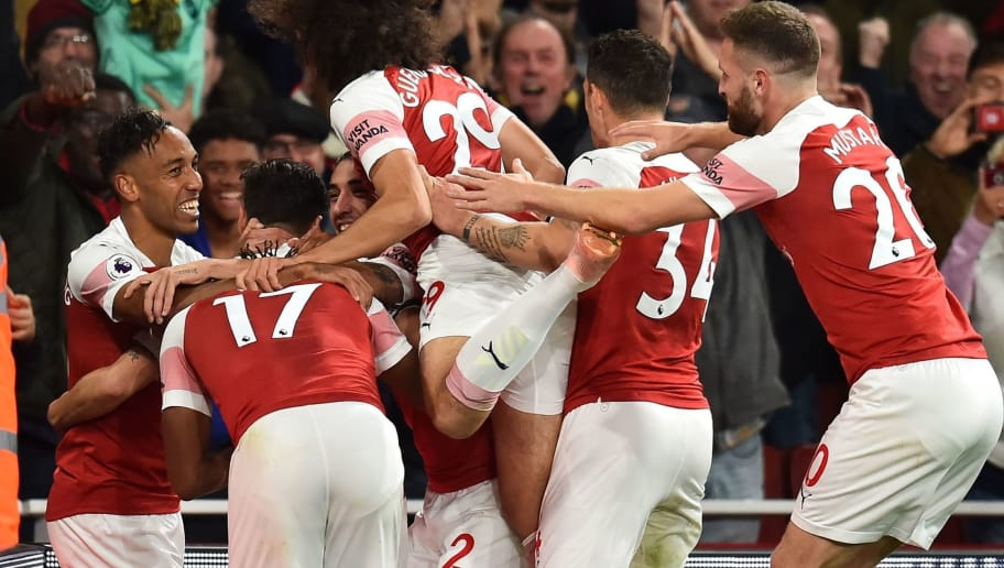 Arsenal's Gabonese striker Pierre-Emerick Aubameyang (L) celebrates with teammates after scoring their third goal during the English Premier League football match between Arsenal and Leicester City at the Emirates Stadium in London on October 22, 2018. (Photo by Glyn KIRK / IKIMAGES / AFP) / RESTRICTED TO EDITORIAL USE. No use with unauthorized audio, video, data, fixture lists, club/league logos or 'live' services. Online in-match use limited to 45 images, no video emulation. No use in betting, games or single club/league/player publications.        (Photo credit should read GLYN KIRK/AFP/Getty Images)