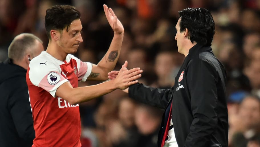 Arsenal's German midfielder Mesut Ozil (L) shakes hands with Arsenal's Spanish head coach Unai Emery (R) after being substituted during the English Premier League football match between Arsenal and Leicester City at the Emirates Stadium in London on October 22, 2018. (Photo by Glyn KIRK / IKIMAGES / AFP) / RESTRICTED TO EDITORIAL USE. No use with unauthorized audio, video, data, fixture lists, club/league logos or 'live' services. Online in-match use limited to 45 images, no video emulation. No use in betting, games or single club/league/player publications.        (Photo credit should read GLYN KIRK/AFP/Getty Images)