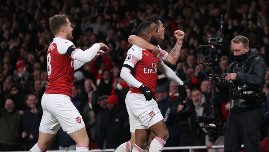 Arsenal's French striker Alexandre Lacazette (C) celebrates with teammates after scoring his team's first goal during the English Premier League football match between Arsenal and Liverpool at the Emirates Stadium in London on November 3, 2018. (Photo by Daniel LEAL-OLIVAS / AFP) / RESTRICTED TO EDITORIAL USE. No use with unauthorized audio, video, data, fixture lists, club/league logos or 'live' services. Online in-match use limited to 120 images. An additional 40 images may be used in extra time. No video emulation. Social media in-match use limited to 120 images. An additional 40 images may be used in extra time. No use in betting publications, games or single club/league/player publications. /         (Photo credit should read DANIEL LEAL-OLIVAS/AFP/Getty Images)