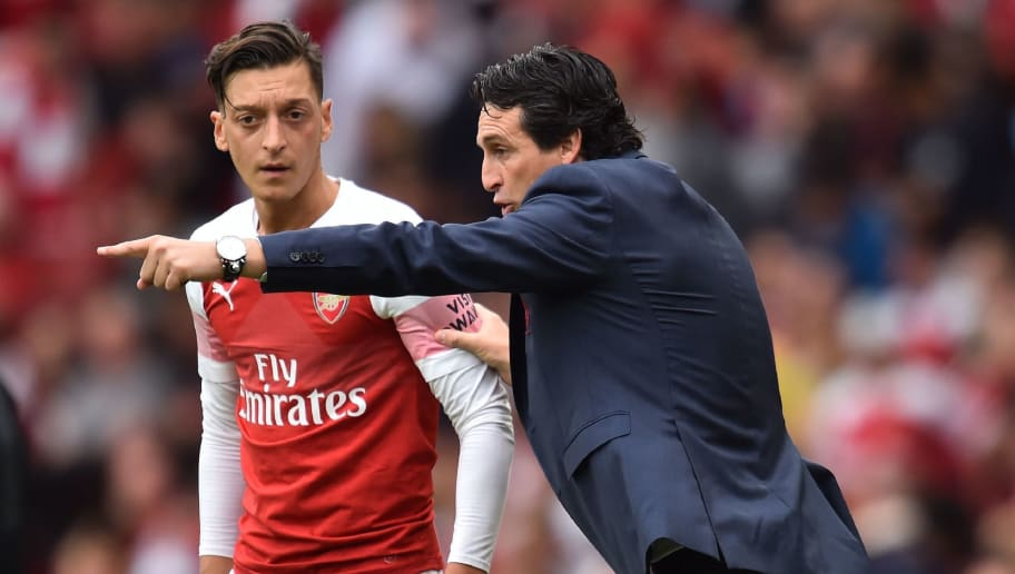 Arsenal's Spanish head coach Unai Emery gestures to Arsenal's German midfielder Mesut Ozil (L) on the touchline during the English Premier League football match between Arsenal and Manchester City at the Emirates Stadium in London on August 12, 2018. (Photo by Glyn KIRK / AFP) / RESTRICTED TO EDITORIAL USE. No use with unauthorized audio, video, data, fixture lists, club/league logos or 'live' services. Online in-match use limited to 120 images. An additional 40 images may be used in extra time. No video emulation. Social media in-match use limited to 120 images. An additional 40 images may be used in extra time. No use in betting publications, games or single club/league/player publications. /         (Photo credit should read GLYN KIRK/AFP/Getty Images)