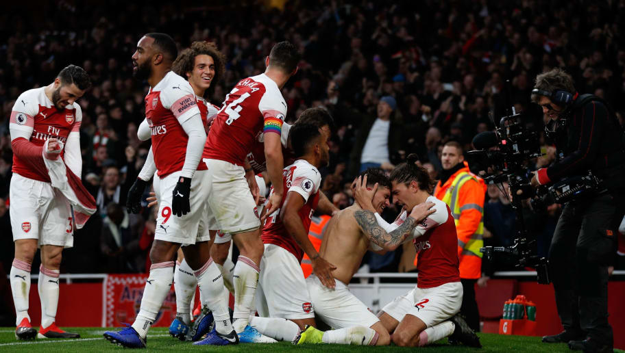 Arsenal's Uruguayan midfielder Lucas Torreira (C) celebrates with teammates after scoring their fourth goal during the English Premier League football match between Arsenal and Tottenham Hotspur at the Emirates Stadium in London on December 2, 2018. - Arsenal won the game 4-2. (Photo by Adrian DENNIS / AFP) / RESTRICTED TO EDITORIAL USE. No use with unauthorized audio, video, data, fixture lists, club/league logos or 'live' services. Online in-match use limited to 120 images. An additional 40 images may be used in extra time. No video emulation. Social media in-match use limited to 120 images. An additional 40 images may be used in extra time. No use in betting publications, games or single club/league/player publications. /         (Photo credit should read ADRIAN DENNIS/AFP/Getty Images)