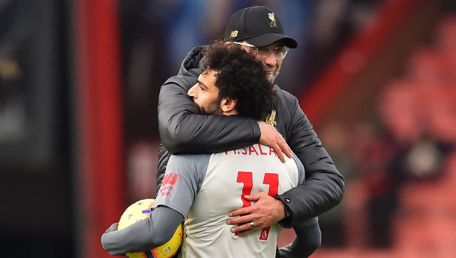 Liverpool's Egyptian midfielder Mohamed Salah (L) holding the match-ball for scoring a hat-trick is embraced by Liverpool's German manager Jurgen Klopp (R) on the pitch after the English Premier League football match between Bournemouth and Liverpool at the Vitality Stadium in Bournemouth, southern England on December 8, 2018. - Liverpool won the game 4-0. (Photo by Glyn KIRK / AFP) / RESTRICTED TO EDITORIAL USE. No use with unauthorized audio, video, data, fixture lists, club/league logos or 'live' services. Online in-match use limited to 120 images. An additional 40 images may be used in extra time. No video emulation. Social media in-match use limited to 120 images. An additional 40 images may be used in extra time. No use in betting publications, games or single club/league/player publications. /         (Photo credit should read GLYN KIRK/AFP/Getty Images)
