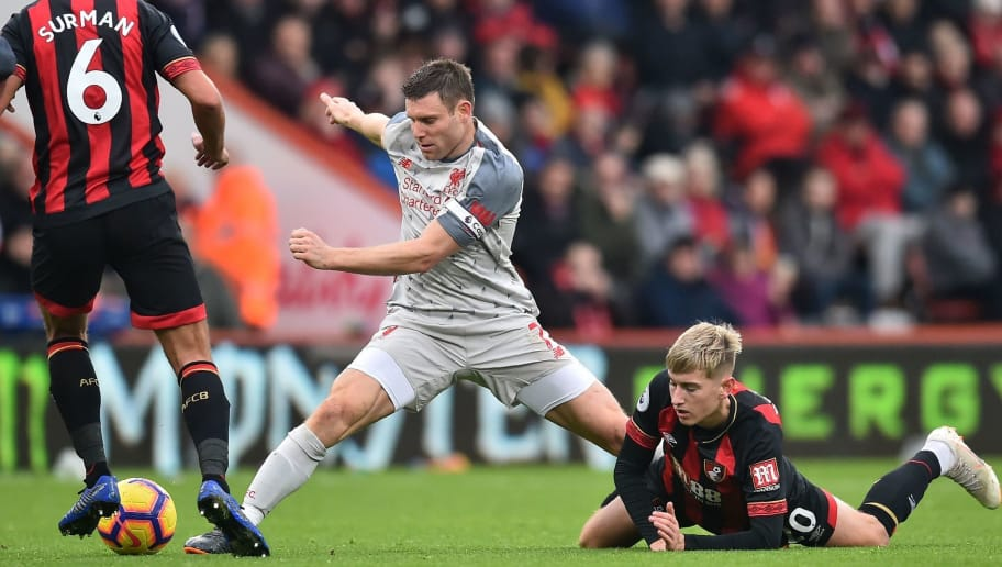 Liverpool's English midfielder James Milner (C) stretches for the ball as Bournemouth's English-born Welsh midfielder David Brooks (R) holds on to his leg during the English Premier League football match between Bournemouth and Liverpool at the Vitality Stadium in Bournemouth, southern England on December 8, 2018. (Photo by Glyn KIRK / AFP) / RESTRICTED TO EDITORIAL USE. No use with unauthorized audio, video, data, fixture lists, club/league logos or 'live' services. Online in-match use limited to 120 images. An additional 40 images may be used in extra time. No video emulation. Social media in-match use limited to 120 images. An additional 40 images may be used in extra time. No use in betting publications, games or single club/league/player publications. /         (Photo credit should read GLYN KIRK/AFP/Getty Images)