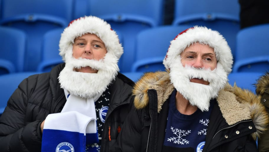 Two Brighton fans dressed as Santa Claus await kick off in the English Premier League football match between Brighton and Hove Albion and Chelsea at the American Express Community Stadium in Brighton, southern England on December 16, 2018. (Photo by Glyn KIRK / AFP) / RESTRICTED TO EDITORIAL USE. No use with unauthorized audio, video, data, fixture lists, club/league logos or 'live' services. Online in-match use limited to 120 images. An additional 40 images may be used in extra time. No video emulation. Social media in-match use limited to 120 images. An additional 40 images may be used in extra time. No use in betting publications, games or single club/league/player publications. /         (Photo credit should read GLYN KIRK/AFP/Getty Images)