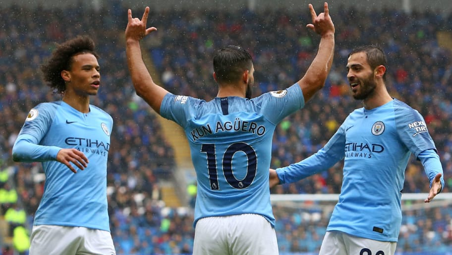 Manchester City's Argentinian striker Sergio Aguero (C) celebrates with Manchester City's German midfielder Leroy Sane (L) and Manchester City's Portuguese midfielder Bernardo Silva (R) after scoring the opening goal of the English Premier League football match between between Cardiff City and Manchester City at Cardiff City Stadium in Cardiff, south Wales on September 22, 2018. (Photo by Geoff CADDICK / AFP) / RESTRICTED TO EDITORIAL USE. No use with unauthorized audio, video, data, fixture lists, club/league logos or 'live' services. Online in-match use limited to 120 images. An additional 40 images may be used in extra time. No video emulation. Social media in-match use limited to 120 images. An additional 40 images may be used in extra time. No use in betting publications, games or single club/league/player publications. /         (Photo credit should read GEOFF CADDICK/AFP/Getty Images)