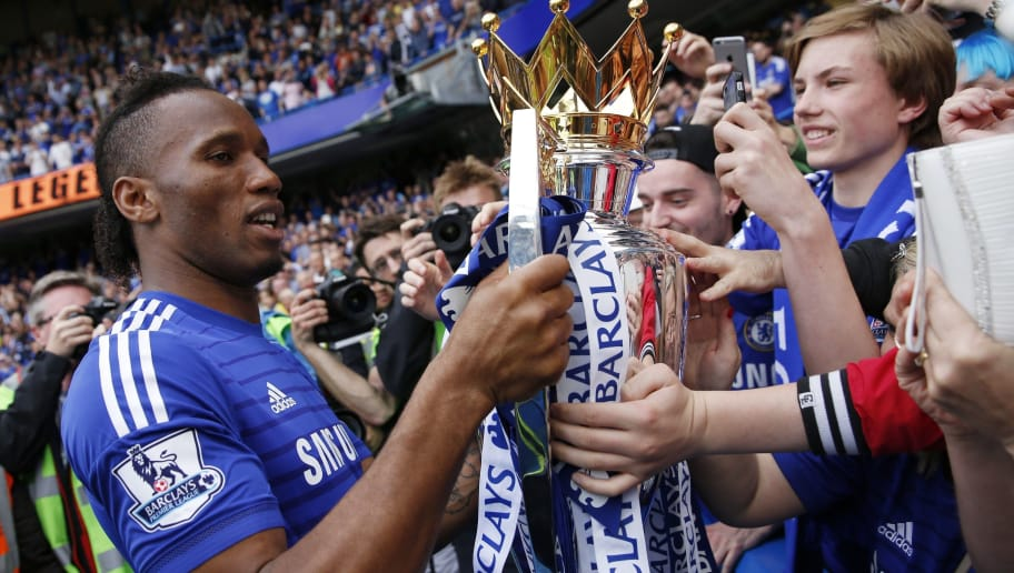 Chelsea's Ivorian striker Didier Drogba shows the Premier League trophy to fans following the presentation after the English Premier League football match between Chelsea and Sunderland at Stamford Bridge in London on May 24, 2015. Chelsea were officially crowned the 2014-2015 Premier League champions.  AFP PHOTO / ADRIAN DENNIS  RESTRICTED TO EDITORIAL USE. NO USE WITH UNAUTHORIZED AUDIO, VIDEO, DATA, FIXTURE LISTS, CLUB/LEAGUE LOGOS OR LIVE SERVICES. ONLINE IN-MATCH USE LIMITED TO 45 IMAGES, NO VIDEO EMULATION. NO USE IN BETTING, GAMES OR SINGLE CLUB/LEAGUE/PLAYER PUBLICATIONS.        (Photo credit should read ADRIAN DENNIS/AFP/Getty Images)