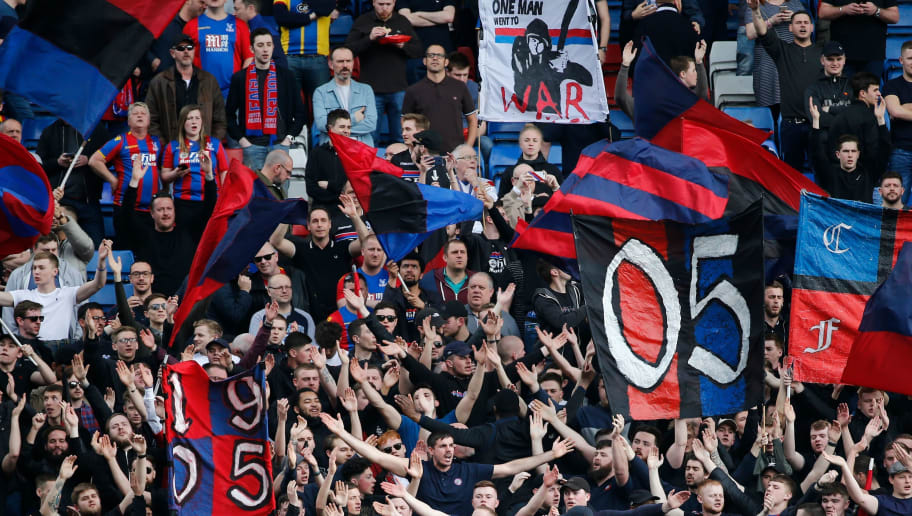 Crystal Palace fans wave flags and sing in the crowd during the English Premier League football match between Crystal Palace and Brighton and Hove Albion at Selhurst Park in south London on April 14, 2018. / AFP PHOTO / Tolga AKMEN / RESTRICTED TO EDITORIAL USE. No use with unauthorized audio, video, data, fixture lists, club/league logos or 'live' services. Online in-match use limited to 75 images, no video emulation. No use in betting, games or single club/league/player publications.  /         (Photo credit should read TOLGA AKMEN/AFP/Getty Images)