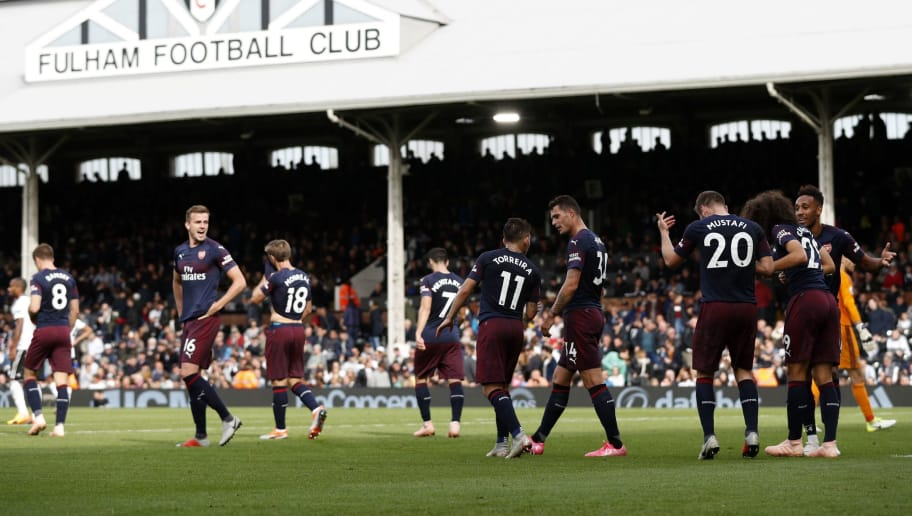 Arsenal's Gabonese striker Pierre-Emerick Aubameyang (R) celebrates with teammates after scoring the team's fifth goal during the English Premier League football match between Fulham and Arsenal at Craven Cottage in London on October 7, 2018. (Photo by Adrian DENNIS / AFP) / RESTRICTED TO EDITORIAL USE. No use with unauthorized audio, video, data, fixture lists, club/league logos or 'live' services. Online in-match use limited to 120 images. An additional 40 images may be used in extra time. No video emulation. Social media in-match use limited to 120 images. An additional 40 images may be used in extra time. No use in betting publications, games or single club/league/player publications. /         (Photo credit should read ADRIAN DENNIS/AFP/Getty Images)