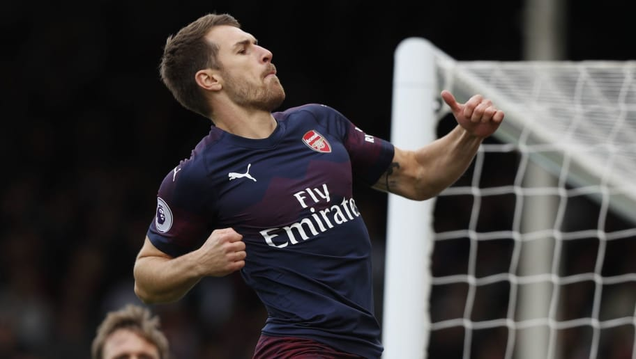Arsenal's Welsh midfielder Aaron Ramsey celebrates after scoring the team's third goal during the English Premier League football match between Fulham and Arsenal at Craven Cottage in London on October 7, 2018. (Photo by Adrian DENNIS / AFP) / RESTRICTED TO EDITORIAL USE. No use with unauthorized audio, video, data, fixture lists, club/league logos or 'live' services. Online in-match use limited to 120 images. An additional 40 images may be used in extra time. No video emulation. Social media in-match use limited to 120 images. An additional 40 images may be used in extra time. No use in betting publications, games or single club/league/player publications. /         (Photo credit should read ADRIAN DENNIS/AFP/Getty Images)