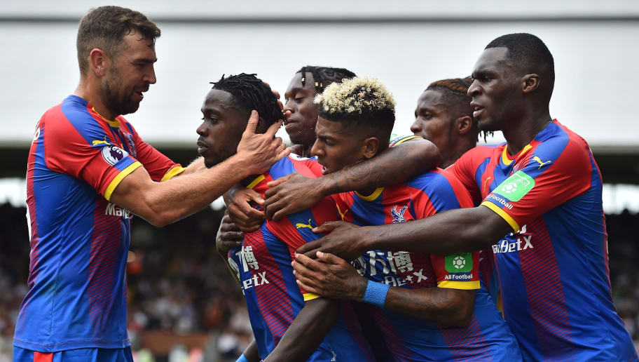 Crystal Palace's German midfielder Jeffrey Schlupp (2L) is mobbed by teammates as he celebrates scoring the opening goal during the English Premier League football match between Fulham and Crystal Palace at Craven Cottage in London on August 11, 2018. (Photo by Glyn KIRK / AFP) / RESTRICTED TO EDITORIAL USE. No use with unauthorized audio, video, data, fixture lists, club/league logos or 'live' services. Online in-match use limited to 75 images, no video emulation. No use in betting, games or single club/league/player publications. /         (Photo credit should read GLYN KIRK/AFP/Getty Images)