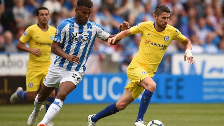 Huddersfield Town's Beninese striker Steve Mounie (L) vies with Chelsea's Italian midfielder Jorginho during the English Premier League football match between Huddersfield Town and Chelsea at the John Smith's stadium in Huddersfield, northern England on August 11, 2018. (Photo by Oli SCARFF / AFP) / RESTRICTED TO EDITORIAL USE.No use with unauthorized audio, video, data, fixture lists, club/league logos or 'live' services. Online in-match use limited to 120 images. An additional 40 images may be used in extra time. No video emulation. Social media in-match use limited to 120 images. An additional 40 images may be used in extra time. No use in betting publications, games or single club/league/player publications/ /         (Photo credit should read OLI SCARFF/AFP/Getty Images)