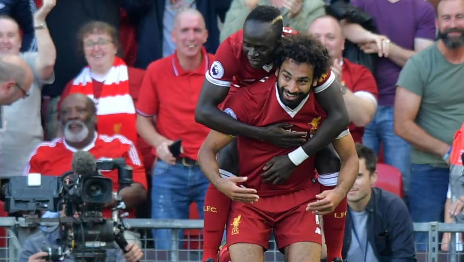 Liverpool's Egyptian midfielder Mohamed Salah (R) celebrates with Liverpool's Senegalese midfielder Sadio Mane after scoring their third goal during the English Premier League football match between Liverpool and Arsenal at Anfield in Liverpool, north west England on August 27, 2017. / AFP PHOTO / Anthony Devlin / RESTRICTED TO EDITORIAL USE. No use with unauthorized audio, video, data, fixture lists, club/league logos or 'live' services. Online in-match use limited to 75 images, no video emulation. No use in betting, games or single club/league/player publications.  /         (Photo credit should read ANTHONY DEVLIN/AFP/Getty Images)