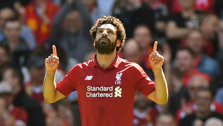 Liverpool's Egyptian midfielder Mohamed Salah celebrates after scoring during the English Premier League football match between Liverpool and Brighton and Hove Albion at Anfield in Liverpool, north west England on May 13, 2018. (Photo by Paul ELLIS / AFP) / RESTRICTED TO EDITORIAL USE. No use with unauthorized audio, video, data, fixture lists, club/league logos or 'live' services. Online in-match use limited to 75 images, no video emulation. No use in betting, games or single club/league/player publications. /         (Photo credit should read PAUL ELLIS/AFP/Getty Images)