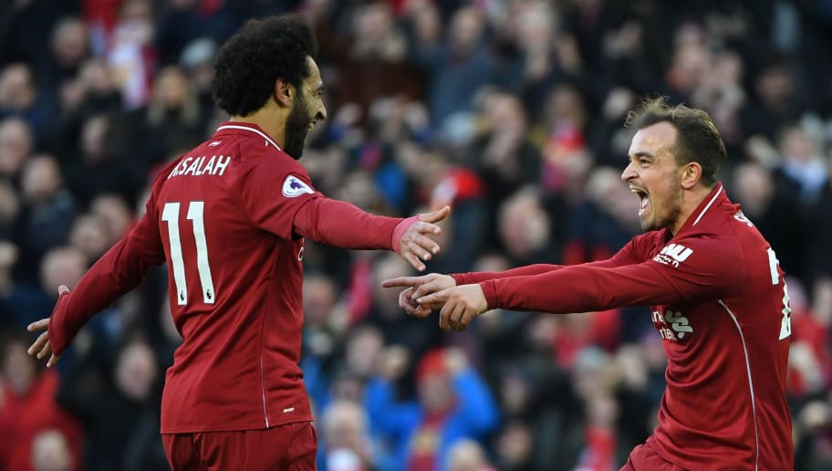 Liverpool's Swiss midfielder Xherdan Shaqiri (R) celebrates scoring their third goal with Liverpool's Egyptian midfielder Mohamed Salah (L) during the English Premier League football match between Liverpool and Cardiff City at Anfield in Liverpool, north west England on October 27, 2018. (Photo by Paul ELLIS / AFP) / RESTRICTED TO EDITORIAL USE. No use with unauthorized audio, video, data, fixture lists, club/league logos or 'live' services. Online in-match use limited to 120 images. An additional 40 images may be used in extra time. No video emulation. Social media in-match use limited to 120 images. An additional 40 images may be used in extra time. No use in betting publications, games or single club/league/player publications. /         (Photo credit should read PAUL ELLIS/AFP/Getty Images)