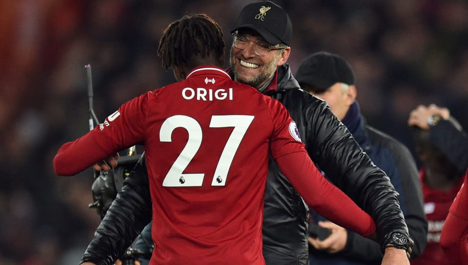 Liverpool's German manager Jurgen Klopp embraces Liverpool's Belgian striker Divock Origi on the pitch after the English Premier League football match between Liverpool and Everton at Anfield in Liverpool, north west England on December 2, 2018. - Liverpool won the game 1-0. (Photo by Oli SCARFF / AFP) / RESTRICTED TO EDITORIAL USE. No use with unauthorized audio, video, data, fixture lists, club/league logos or 'live' services. Online in-match use limited to 120 images. An additional 40 images may be used in extra time. No video emulation. Social media in-match use limited to 120 images. An additional 40 images may be used in extra time. No use in betting publications, games or single club/league/player publications. /         (Photo credit should read OLI SCARFF/AFP/Getty Images)