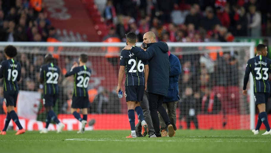 Manchester City's Spanish manager Pep Guardiola talks with Manchester City's Algerian midfielder Riyad Mahrez as they leave the pitch following the English Premier League football match between Liverpool and Manchester City at Anfield in Liverpool, north west England on October 7, 2018. - The match ended in a draw 0-0. (Photo by Paul ELLIS / AFP) / RESTRICTED TO EDITORIAL USE. No use with unauthorized audio, video, data, fixture lists, club/league logos or 'live' services. Online in-match use limited to 120 images. An additional 40 images may be used in extra time. No video emulation. Social media in-match use limited to 120 images. An additional 40 images may be used in extra time. No use in betting publications, games or single club/league/player publications. /         (Photo credit should read PAUL ELLIS/AFP/Getty Images)