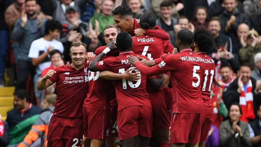 Liverpool's German-born Cameroonian defender Joel Matip  celebrates with teammates after scoring the team's second goal during the English Premier League football match between Liverpool and Southampton at Anfield in Liverpool, north west England on September 22, 2018. (Photo by Paul ELLIS / AFP) / RESTRICTED TO EDITORIAL USE. No use with unauthorized audio, video, data, fixture lists, club/league logos or 'live' services. Online in-match use limited to 120 images. An additional 40 images may be used in extra time. No video emulation. Social media in-match use limited to 120 images. An additional 40 images may be used in extra time. No use in betting publications, games or single club/league/player publications. /         (Photo credit should read PAUL ELLIS/AFP/Getty Images)