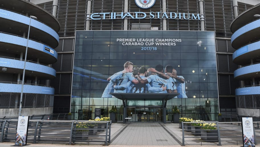 A new poster showing members of the Manchester City team celebrating has been placed at the entrance to the Etihad Stadium in Manchester, north west England to celebrate Manchester City winning the Premier League title on April 16, 2018. Pep Guardiola's side were crowned kings of English football yesterday as their arch rivals Manchester United slumped to a shock 1-0 defeat against struggling West Bromwich Albion. / AFP PHOTO / Paul ELLIS / RESTRICTED TO EDITORIAL USE. No use with unauthorized audio, video, data, fixture lists, club/league logos or 'live' services. Online in-match use limited to 75 images, no video emulation. No use in betting, games or single club/league/player publications.  /         (Photo credit should read PAUL ELLIS/AFP/Getty Images)