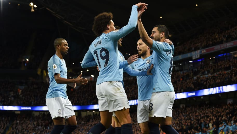 Manchester City's German midfielder Ilkay Gundogan (R) celebrates scoring their third goal for 3-1 with Manchester City's German midfielder Leroy Sane (C) during the English Premier League football match between Manchester City and Bournemouth at the Etihad Stadium in Manchester, north west England, on December 1, 2018. (Photo by Paul ELLIS / AFP) / RESTRICTED TO EDITORIAL USE. No use with unauthorized audio, video, data, fixture lists, club/league logos or 'live' services. Online in-match use limited to 120 images. An additional 40 images may be used in extra time. No video emulation. Social media in-match use limited to 120 images. An additional 40 images may be used in extra time. No use in betting publications, games or single club/league/player publications. /         (Photo credit should read PAUL ELLIS/AFP/Getty Images)