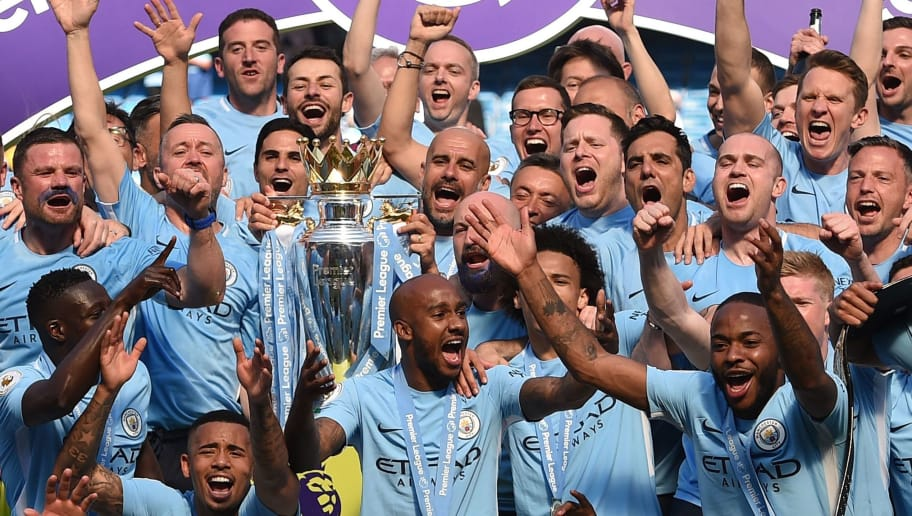 Manchester City's Spanish manager Pep Guardiola (C) holds the Premier League trophy on the pitch with Manchester City players after the English Premier League football match between Manchester City and Huddersfield Town at the Etihad Stadium in Manchester, north west England, on May 6, 2018. (Photo by Oli SCARFF / AFP) / RESTRICTED TO EDITORIAL USE. No use with unauthorized audio, video, data, fixture lists, club/league logos or 'live' services. Online in-match use limited to 75 images, no video emulation. No use in betting, games or single club/league/player publications. /         (Photo credit should read OLI SCARFF/AFP/Getty Images)