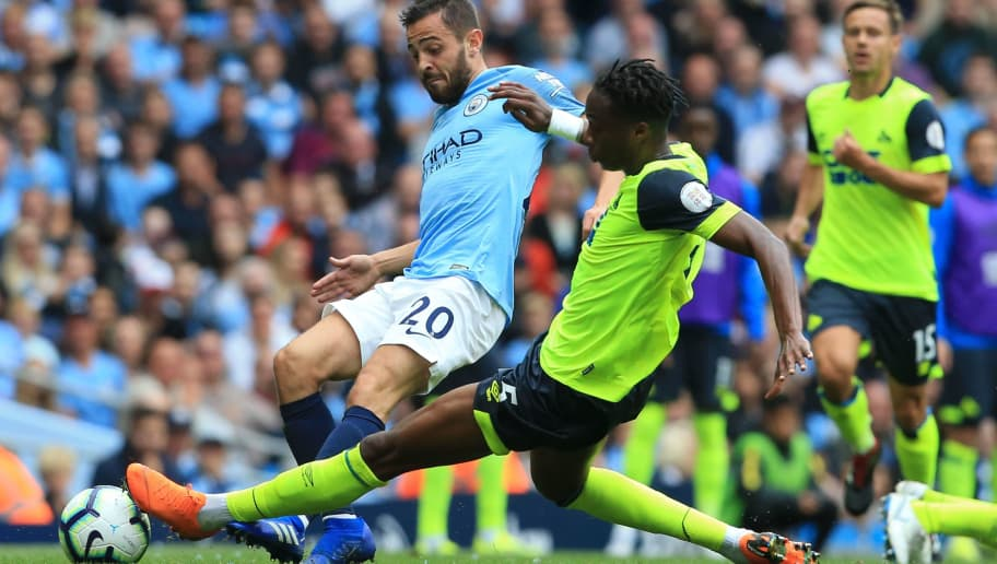 Huddersfield Town's Swiss-born Dutch defender Terence Kongolo (R) tackles Manchester City's Portuguese midfielder Bernardo Silva (L) during the English Premier League football match between Manchester City and Huddersfield Town at the Etihad Stadium in Manchester, north west England, on August 19, 2018. (Photo by Lindsey PARNABY / AFP) / RESTRICTED TO EDITORIAL USE. No use with unauthorized audio, video, data, fixture lists, club/league logos or 'live' services. Online in-match use limited to 120 images. An additional 40 images may be used in extra time. No video emulation. Social media in-match use limited to 120 images. An additional 40 images may be used in extra time. No use in betting publications, games or single club/league/player publications. /         (Photo credit should read LINDSEY PARNABY/AFP/Getty Images)