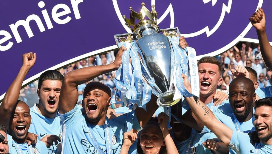 Manchester City's captain, Belgian defender Vincent Kompany (centre left) and Manchester City's Argentinian striker Sergio Aguero (R) lift up the Premier League trophy as they celebrate on the pitch after the English Premier League football match between Manchester City and Huddersfield Town at the Etihad Stadium in Manchester, north west England, on May 6, 2018. (Photo by Paul ELLIS / AFP) / RESTRICTED TO EDITORIAL USE. No use with unauthorized audio, video, data, fixture lists, club/league logos or 'live' services. Online in-match use limited to 75 images, no video emulation. No use in betting, games or single club/league/player publications. /         (Photo credit should read PAUL ELLIS/AFP/Getty Images)