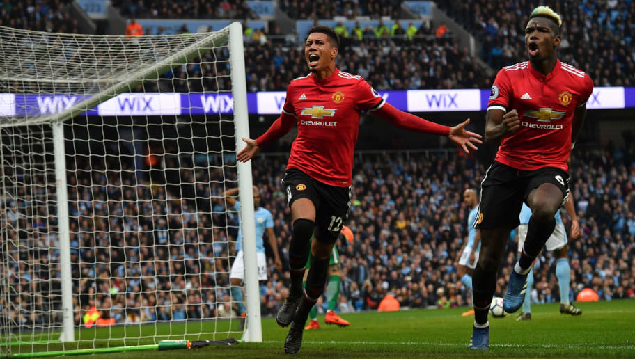 Manchester United's English defender Chris Smalling (L) celebrates scoring their third goal with Manchester United's French midfielder Paul Pogba (R) during the English Premier League football match between Manchester City and Manchester United at the Etihad Stadium in Manchester, north west England, on April 7, 2018. / AFP PHOTO / Ben STANSALL / RESTRICTED TO EDITORIAL USE. No use with unauthorized audio, video, data, fixture lists, club/league logos or 'live' services. Online in-match use limited to 75 images, no video emulation. No use in betting, games or single club/league/player publications.  /         (Photo credit should read BEN STANSALL/AFP/Getty Images)